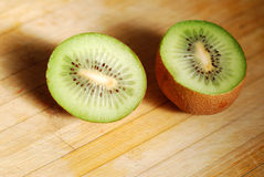 Cut by a kiwi on chopping board Royalty Free Stock Images