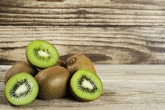 Cut kiwi folded in a pile on a wood background royalty free stock photography