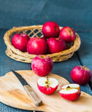 Cut with a knife fresh red apples on a wooden board, fruits Stock Image