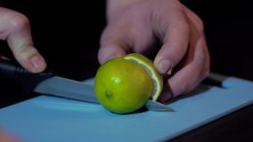 Cut with a knife lime. Cut lime with a knife on a blue board stock footage