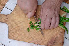 Cut with a knife raw green beans on a wooden board,. Women hand with a knife cutting raw green beans on a wooden kitchen board Stock Photo