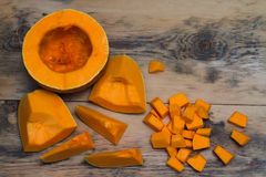 Cut into large and small pieces of pumpkin on a wooden backgroun Royalty Free Stock Photos