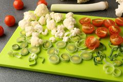 Cut leeks, cherry tomatoes and cauliflower on cutting board. Fresh vegetables sliced on bright green board Royalty Free Stock Photography