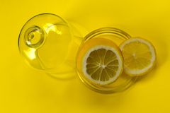 Cut lemon in glassware on yellow  backgroundCopy space royalty free stock image