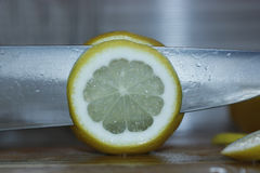 Cut a lemon with a knife. Royalty Free Stock Image