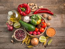 Cut lemot and pepper, fresh veggies, topview. Cut lemon and pepper, peanuts and fresh veggies lying on the table, topview Royalty Free Stock Photography