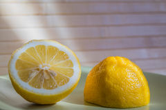Cut a lemon in the sun. On a green plate Stock Photo