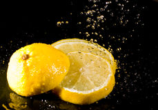 Cut lemon under water splashes Stock Images