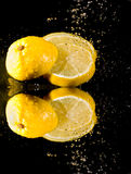Cut lemon under water splashes Stock Photography