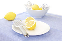 Lemons and zester on a white plate. Cut lemons on a white bowl with lemon steel lemon zester. White bowl with uncut lemons in the background Royalty Free Stock Image