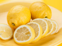 Cut lemons on yellow porcelain Royalty Free Stock Photos