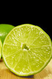 Cut Limes on Bamboo Background. Stock Photos