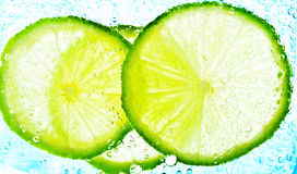 Cut limes in the water Royalty Free Stock Photos