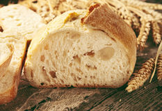 Cut loaf of bread with ears of wheat Royalty Free Stock Photo