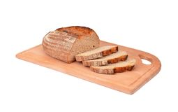 The cut loaf of bread on wooden board Stock Images