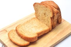 The cut loaf of bread on the wooden cutting board on the white background. Royalty Free Stock Image