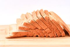 The cut loaf of breadon white Background. The cut loaf of bread on Wood block  on white Background Stock Images