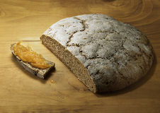 Cut loaf of fresh baked rye bread with orange marmalade. On wooden background Stock Photos