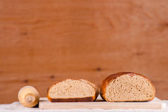 Cut loaf of fresh bread on burlap on wooden table Stock Images