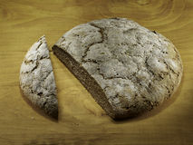 Cut loaf of rye bread. On wooden background Royalty Free Stock Image