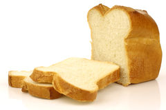 Cut loaf of white bread and some slices Royalty Free Stock Images