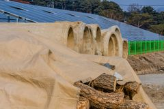 Cut logs and precast concrete culvert sections. Cut logs covered with tarp in front of precast concrete culvert sections with array of solar panels and trees in Royalty Free Stock Photography