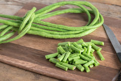 Cut of long bean on wood cutting board. Selective focus. Royalty Free Stock Photography