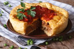 Cut meat pie on a plate close-up. Horizontal Stock Photos