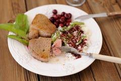Cut medium rare steak with rice, berry sauce and chard Stock Image