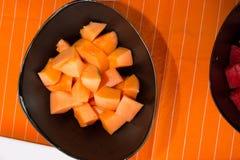 Cut melon on the black plate under orange napkin Royalty Free Stock Images