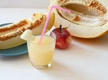 Cut the melon next to the red apples, a glass of smoothie with a slice of melon with a straw royalty free stock photo