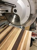Cut off saw cutting a board. Cut off saw cutting on board in a wood working shop royalty free stock image