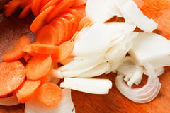 Cut onion and carrot on chopping board Royalty Free Stock Photography