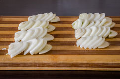 Cut onion half rings on a cutting board for cooking Stock Photo