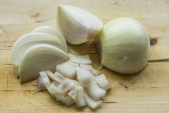 Cut onion. An onion cut on a wooden cutting board. Various stages in the cutting process Stock Photos