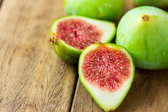 Cut open halved ripe green fig with red pulp. Aged plank wood background. Copy space. For text Royalty Free Stock Photos