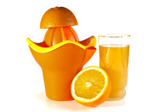 The cut orange on a juice extractor and a juice glass Royalty Free Stock Photos