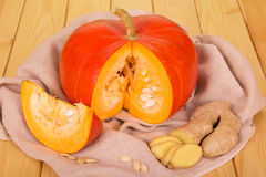 Cut orange pumpkin with ginger on wooden background Stock Photos