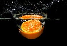 Cut orange splashing in the water. Stock Image