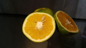 Orange halves with dark background. Cut oranges with green peels and seeds with a dark background on reflective surface, centered stock images