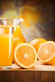 Cut oranges and juice in glass. Oranges and juice of oranges in glass and jug on wooden boards stock photo