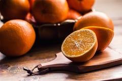 Cut oranges. Pressed orange manual method. Oranges and sliced oranges with juice and squeezer. Stock Photos