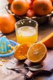 Cut oranges. Pressed orange manual method. Oranges and sliced oranges with juice and squeezer. Stock Images