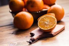 Cut oranges. Pressed orange manual method. Oranges and sliced oranges with juice and squeezer. Stock Photo