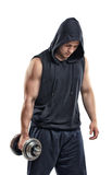 Cut-out athletic young guy in hoodie lifting a dumbbell bulging biceps. Biceps Exercises. Self-perfection. Self improvement. Power training. Healthy lifestyle Royalty Free Stock Photo
