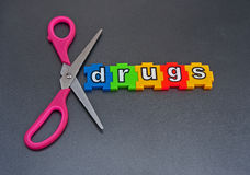 Cut out drugs. Text ' Cut out drugs ' in colorful jigsaw style letters with pink handled scissors to emphasize cutting  on dark background Royalty Free Stock Photos