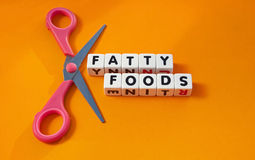 Cut out fatty foods. Text ' fatty foods ' inscribed in black uppercase letters on small white cubes with scissors to symbolize cut out , orange background Royalty Free Stock Photo