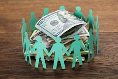Cut-out Figures Around The Hundred Dollar Bill. Crowdfunding Concept. Paper Cut Out Human Figures Around The Stack Of Hundred Dollar Bills Stock Photography