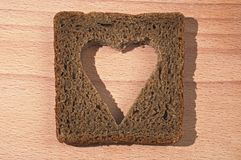 The cut out heart on a piece of brown bread Stock Photography