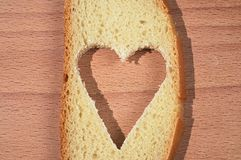 The cut out heart on a piece of white bread Stock Images